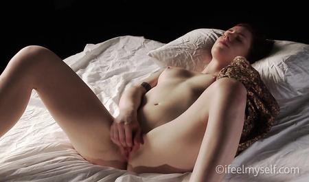 Телка с растрепанными волосами мастурбирует манду на кровати перед сном