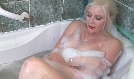 Грудастая блонда от души дрочит письку в ванной комнате